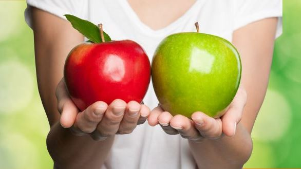 Someone holding a red apple and a green apple side by side