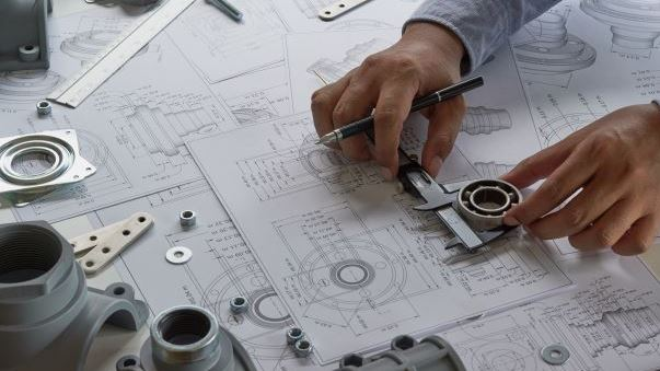 Engineer looking at drawings and components