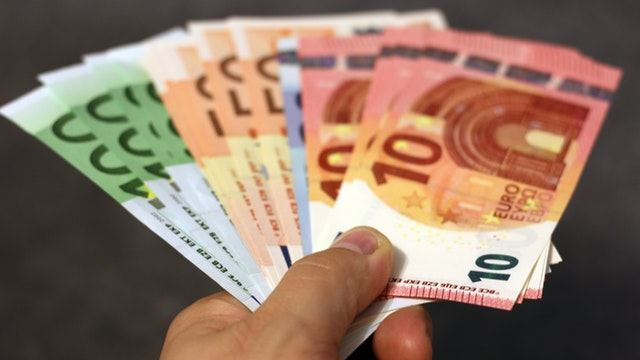 Irish businessman's hand with cash, euro banknotes